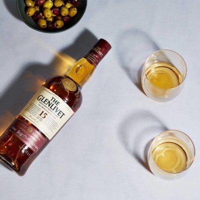 Glenlivet on table with olives and glasses